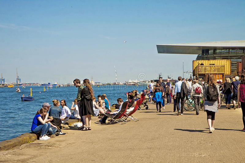 Copenhagen, Denmark - people eating and sitting in the sun on Paper Island. Copenhagen - people enjoy the beautiful weekend weather on the waterfront of stock photography