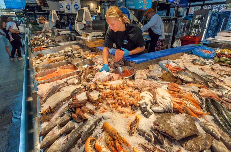 Women selling marine reptiles, fish, crayfish, octopuses and other sea products on the urban food market. COPENHAGEN, DENMARK - SEPT 5: Women selling marine royalty free stock photography