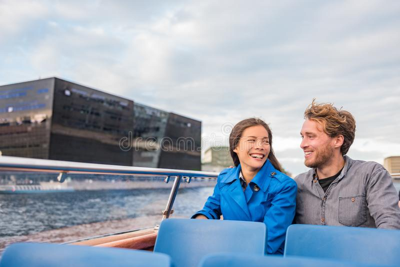 Copenhagen tourists couple on city boat cruise tour enjoying view of the black diamond Royal library, famous architecture building stock images
