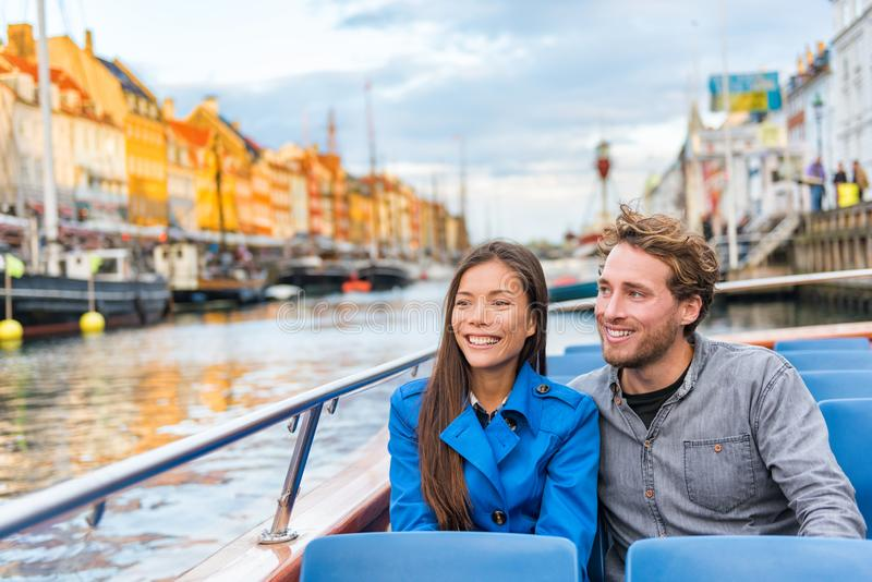 Copenhagen tourists people on Denmark travel holiday cruise boat tour in old port. Young multiracial couple travelers relaxing stock photography