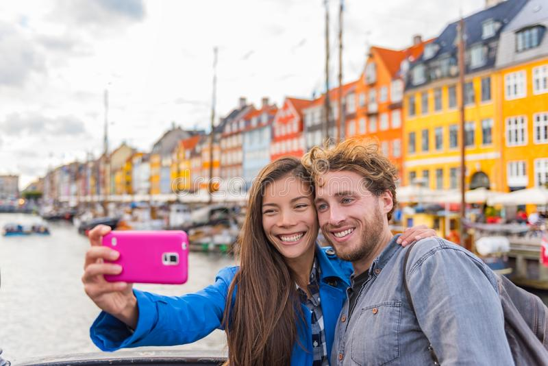 Copenhagen travel couple tourists taking selfie photo with phone camera. Smiling young people students at old port Nyhavn, tourism stock images