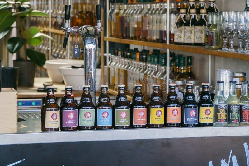 Copenhague, Dinamarca - 6 de mayo de 2018: Fila de las botellas de cerveza coloridas en el escaparate de la tienda de la calle en imagenes de archivo