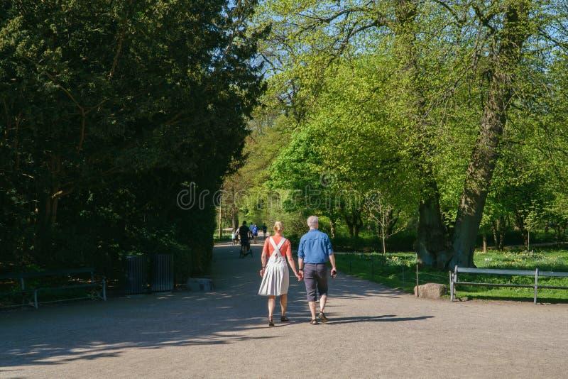Copenhague, Dinamarca - 6 de mayo de 2018: Gente walmking en paisaje pacífico del parque en un día soleado hermoso de la primaver fotos de archivo libres de regalías