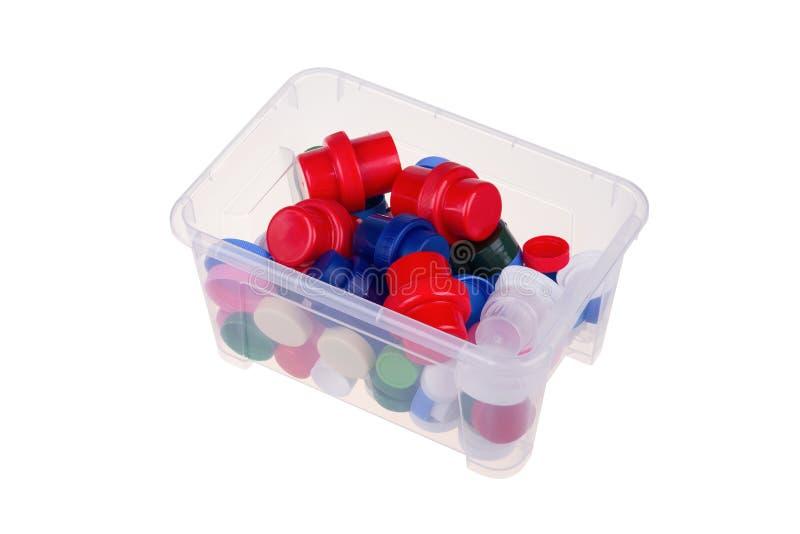 Coperchi di plastica variopinti in una scatola isolata su fondo bianco, con il percorso di ritaglio fotografie stock
