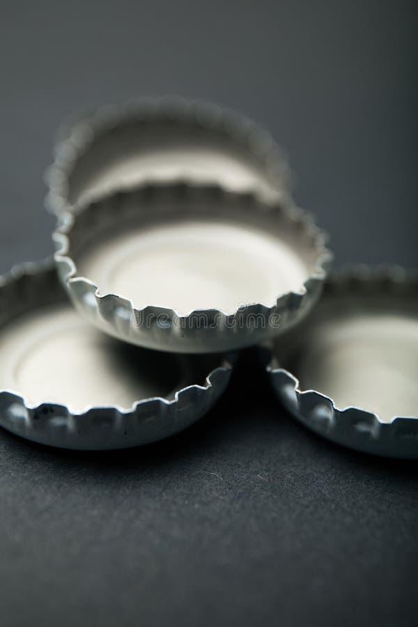 Coperchi sparsi dalle bottiglie di birra su un fondo nero fotografie stock