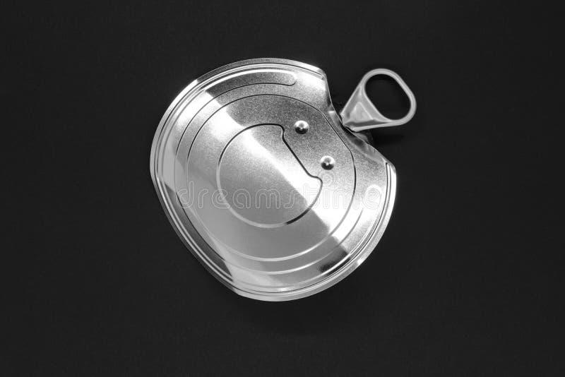 Coperchio d'argento aperto e piegato della latta di alluminio su fondo nero fotografia stock