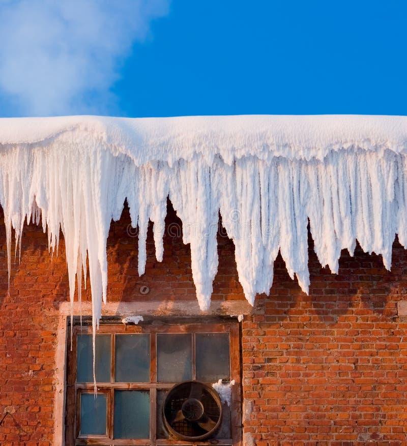 Coperchio di neve sul tetto di vecchio tessuto di tessile con i ghiaccioli, cielo blu fotografie stock libere da diritti