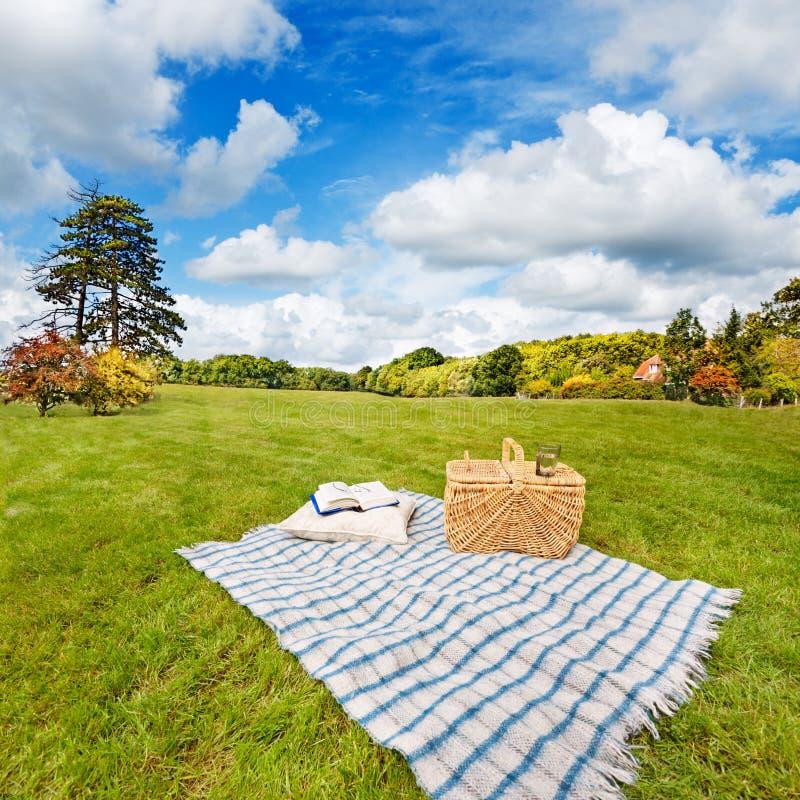 Coperta & cestino di picnic nel campo pieno di sole immagine stock
