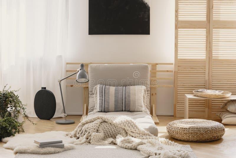 Coperta calda bianca e cuscino modellato sul futon beige nell'interno naturale alla moda della camera da letto, foto reale con il fotografia stock libera da diritti