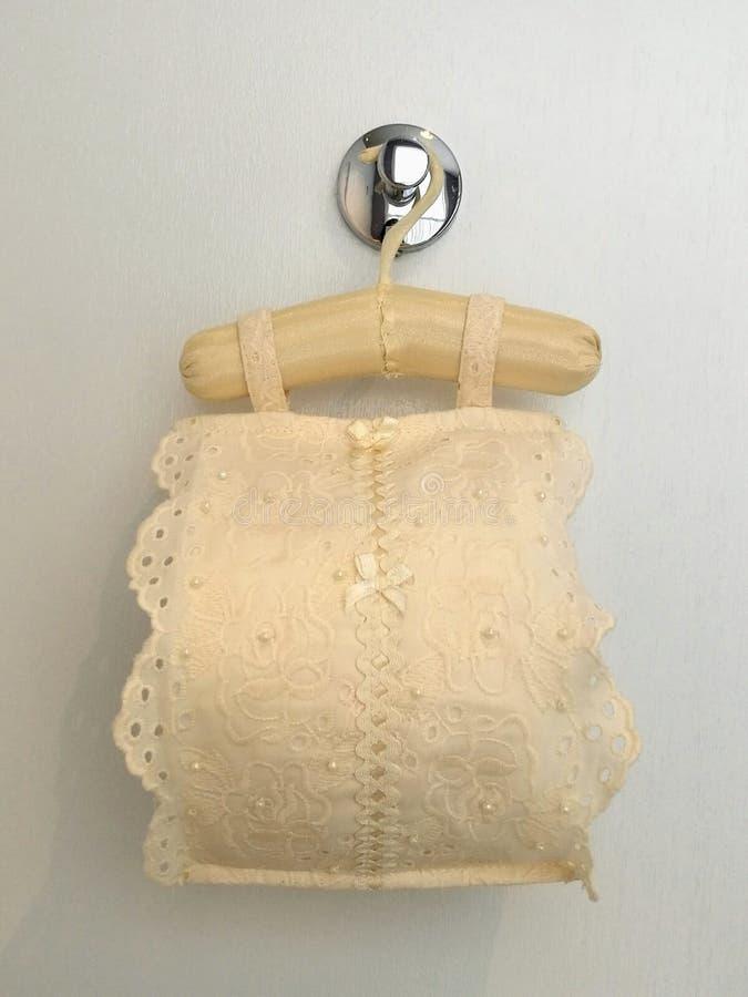 Coperta di tela del pizzo del panno del tessuto del rotolo con il rotolo della carta igienica per l'interno sanitario che appende immagine stock