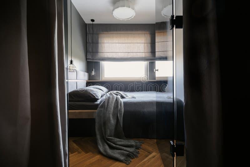 Coperta e cuscini grigi sul letto nell'interno semplice della camera da letto dell'hotel fotografia stock libera da diritti