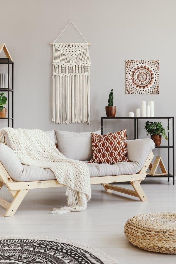 Coperta e cuscino sullo strato nel salone di boho immagini stock