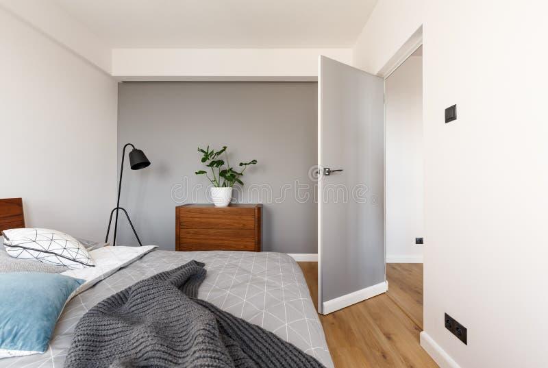 Coperta grigia sul letto nell'interno minimo della camera da letto con la pianta sul wo fotografie stock libere da diritti