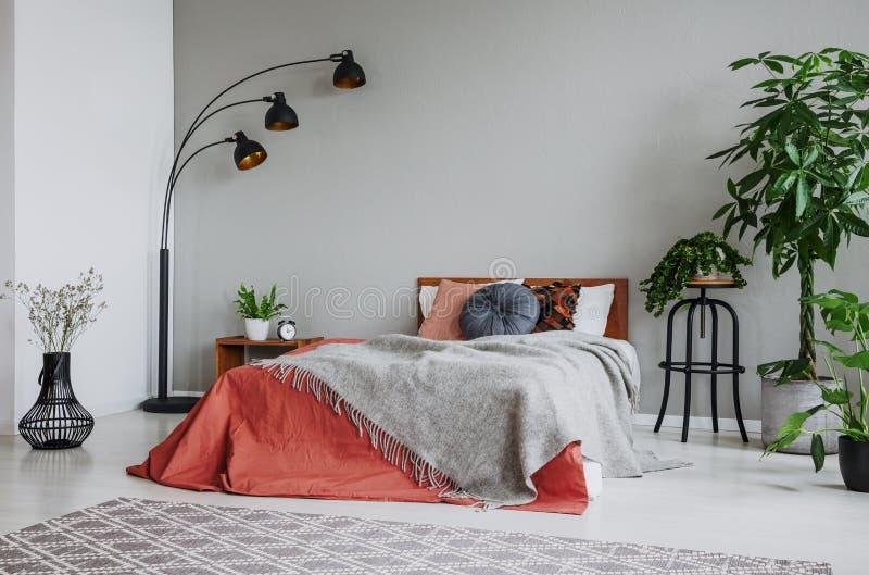 Coperta grigia sul letto rosso fra le piante e la lampada nell'interno della camera da letto con tappeto fotografia stock libera da diritti