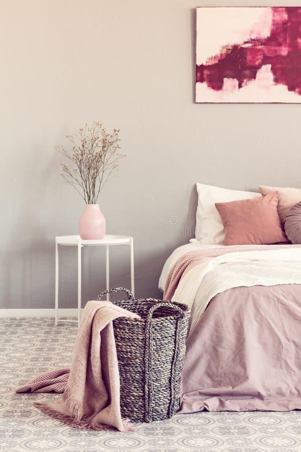 Coperta rosa pastello sul canestro di vimini nell'interno alla moda della camera da letto fotografie stock libere da diritti