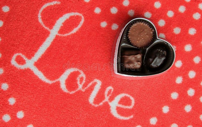 Coperta rossa con l'amore di parola scritto secondo copione attraverso la cima ed il trio del cioccolato fotografia stock libera da diritti