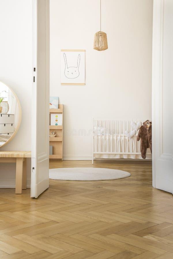 Coperta rotonda bianca accanto alla culla del ` s del bambino nell'interno della camera da letto con il manifesto ed i cuscini de immagini stock