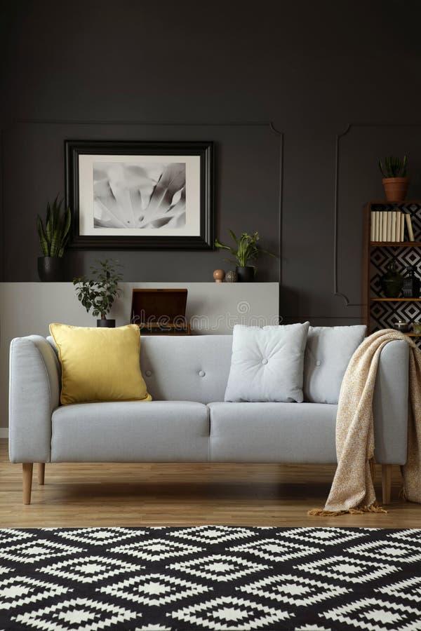 Coperta sul divano grigio con il cuscino giallo nell'interno del salone con tappeto ed il manifesto Foto reale fotografie stock libere da diritti