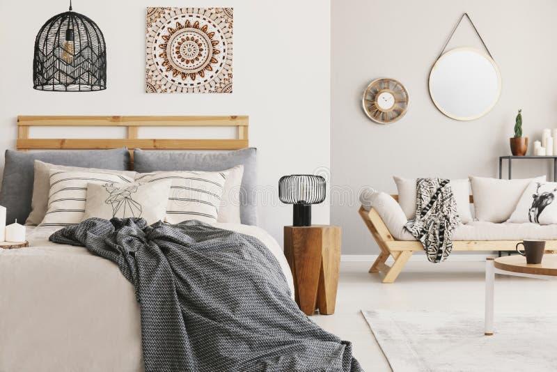 Coperta sul letto sotto la lampada e panchetto di legno nella camera da letto di boho interna con il manifesto ed il sofà immagini stock libere da diritti