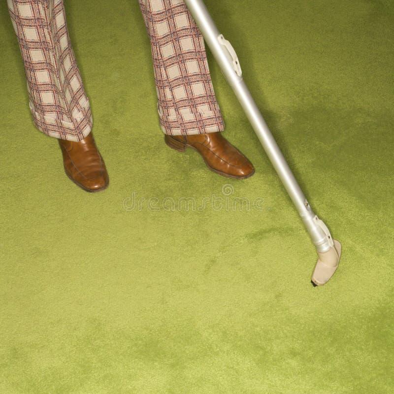 Coperta vacuuming dell'uomo. immagini stock libere da diritti