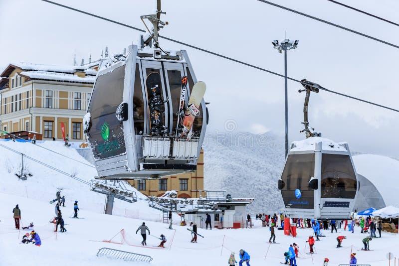 Coperto di sci della neve pende e di ascensori della teleferica nella località di soggiorno di montagna dell'inverno di Gorkij Go fotografia stock