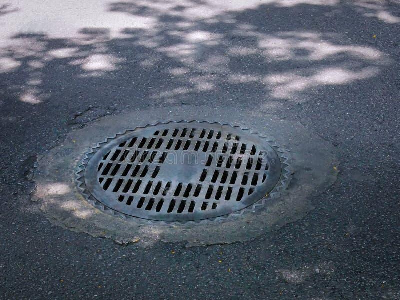 Copertura della botola rotonda con la griglia del metallo per drenaggio dell'acqua piovana immagini stock libere da diritti