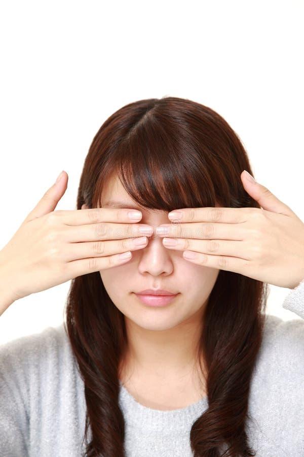Copertura della donna il suo fronte con le mani fotografia stock libera da diritti
