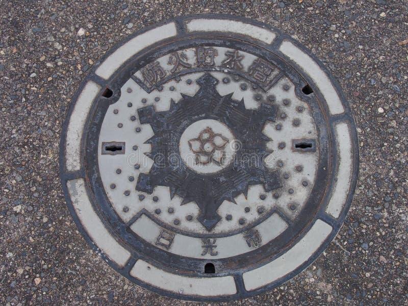 Copertura dello scolo della botola sulla via a Nikko, Giappone fotografia stock