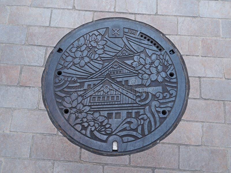 Copertura dello scolo della botola sulla via a Osaka, Giappone fotografia stock libera da diritti