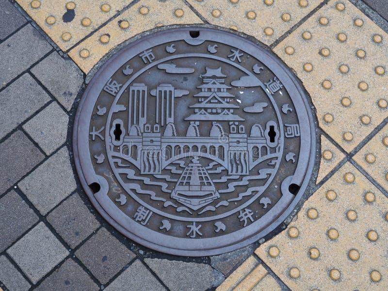 Copertura dello scolo della botola sulla via a Osaka, Giappone immagini stock libere da diritti