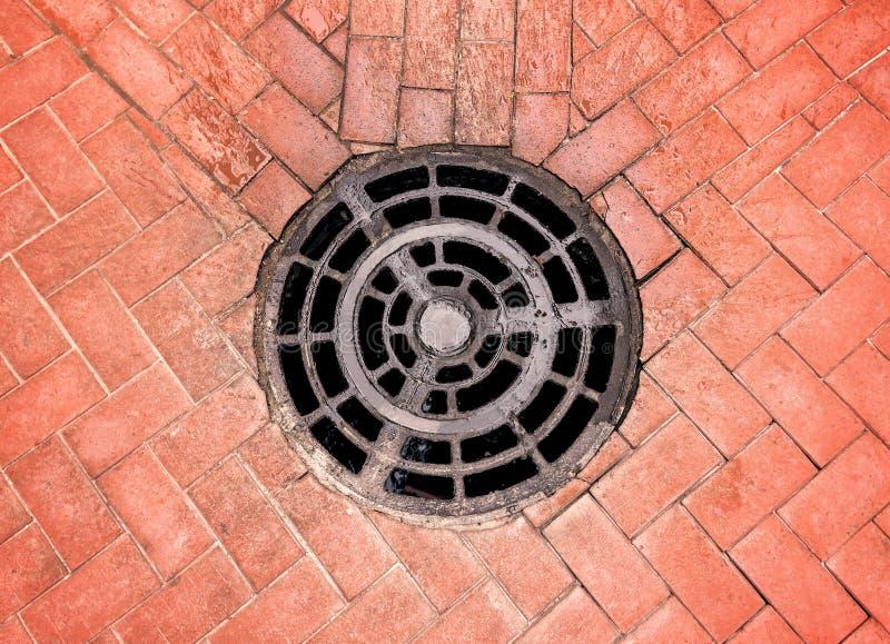 Copertura di botola rotonda della fogna in pavimentazione della via immagine stock