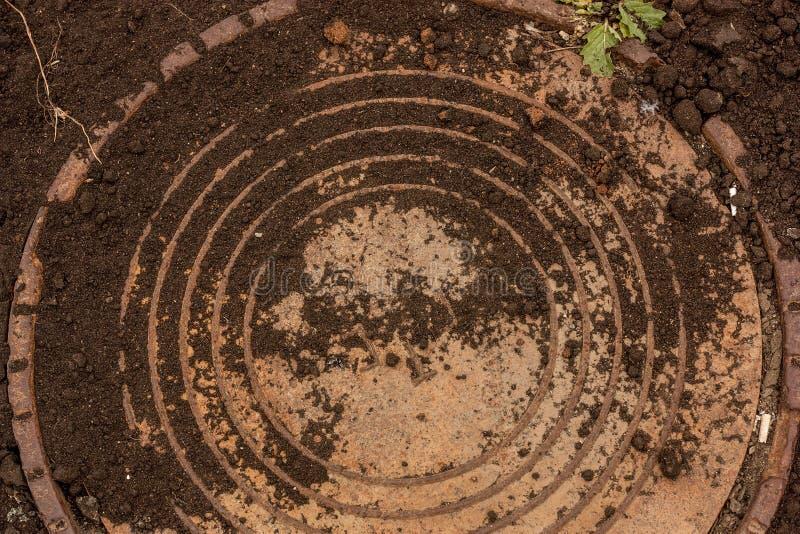 Copertura di botola rotonda della fogna in terra urbana grungy fotografia stock