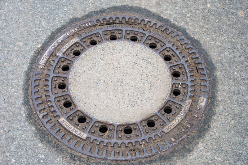 Copertura di botola rotonda sul sentiero per pedoni fotografie stock libere da diritti