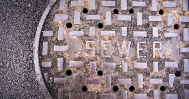 Copertura scaricata Asphalt Side Street Water Drain della conduttura di fogna della botola fotografia stock libera da diritti