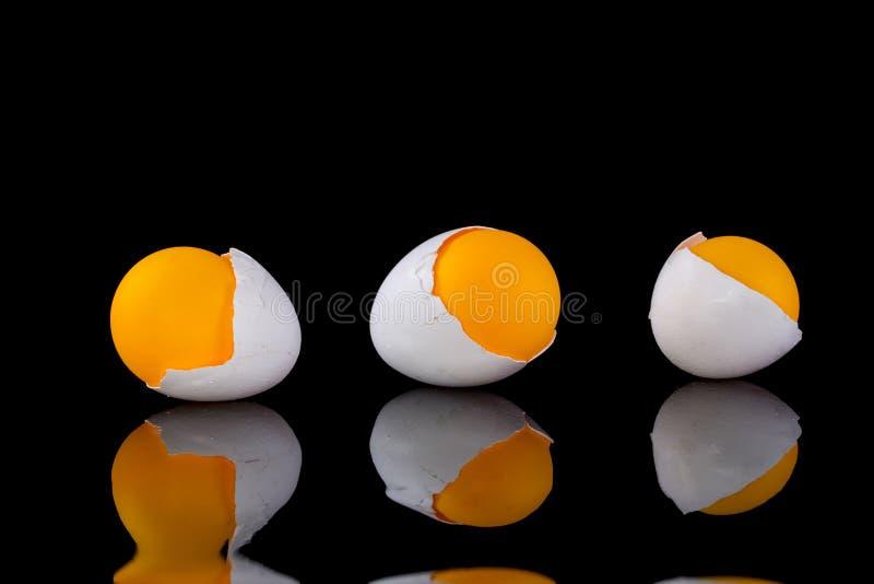 Coperture dell'uovo con la palla arancio su un fondo nero immagini stock