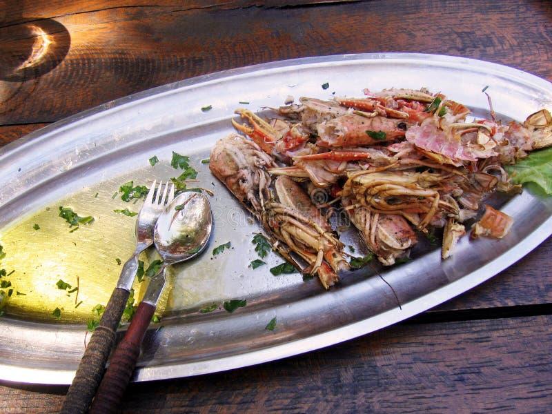 Coperture di grandi gamberetti alimentari, fritte in olio d'oliva con aglio e prezzemolo su un piatto del metallo Tavola di legno fotografia stock