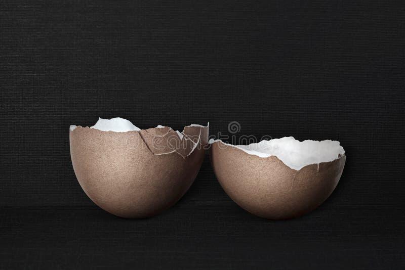 Coperture rotte dell'uovo su un fondo nero del tessuto immagine stock