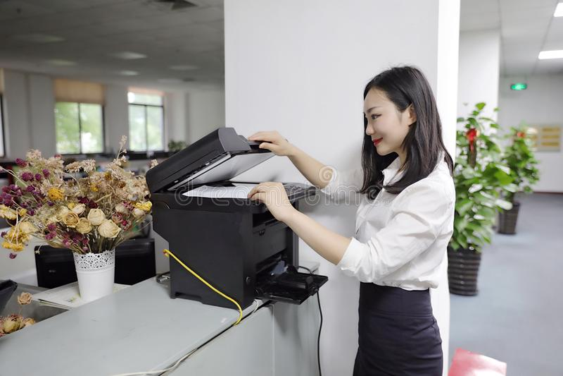 Copiadora china de la impresora del uso del papel de copia de la impresión de la muchacha de la mujer de la señora de la oficina  imagen de archivo