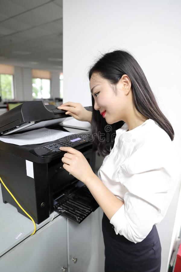 Copiadora china de la impresora del uso del papel de copia de la impresión de la muchacha de la mujer de la señora de la oficina  fotografía de archivo