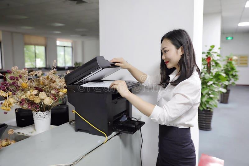 Copiadora chinesa da impressora do uso do papel de cópia da cópia da menina da mulher da senhora do escritório de Ásia no local d imagem de stock
