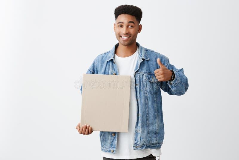 Copie el espacio Ciérrese para arriba de estudiante masculino negro-pelado los jóvenes alegres con el peinado afro en la tenencia imagen de archivo libre de regalías
