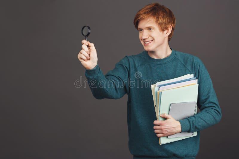 Copie el espacio El retrato del estudiante masculino alegre hermoso joven que sonríe con los dientes, sosteniendo la porción de p imagenes de archivo