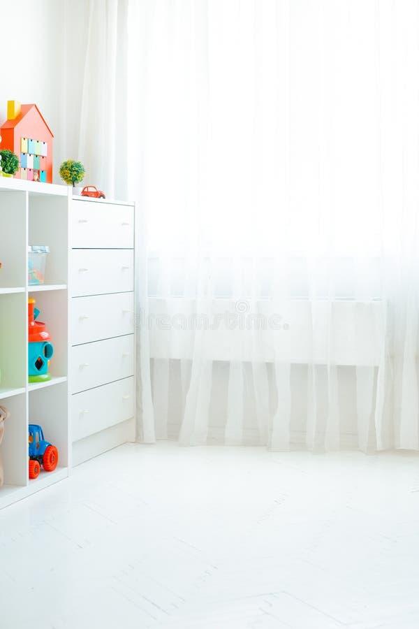 Copie o espaço de uma parede vazia em uma sala de crianças simples com um assoalho de madeira branco e uma grande e janela clara imagem de stock