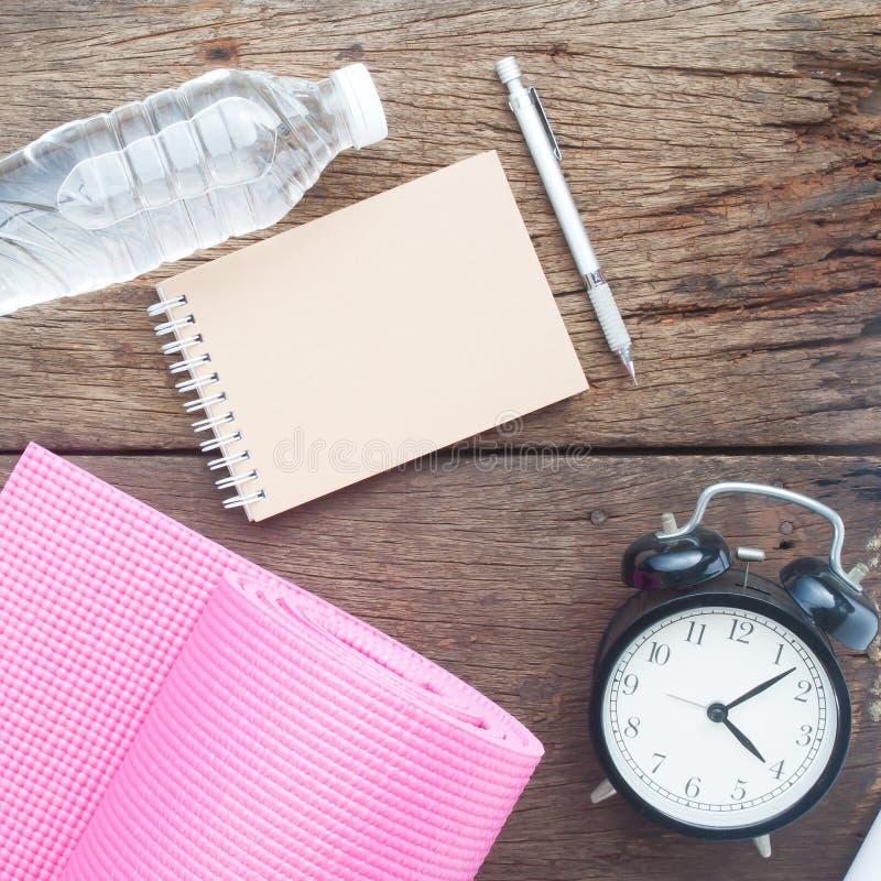 Copie o espaço no caderno do ofício com água, a esteira da ioga e o cloc do alarme fotografia de stock royalty free