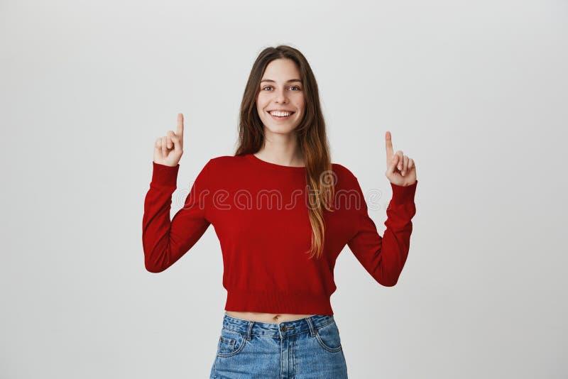 Copie o espaço Retrato isolado do estúdio da moça bonita alegre com cabelo escuro na camiseta e em calças de brim vermelhas que s imagem de stock