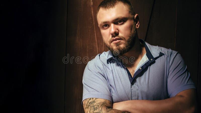 Copie o espaço, seu texto aqui, o homem farpado brutal com uma tatuagem em seu braço, retrato de um homem na luz dramática contra fotografia de stock royalty free