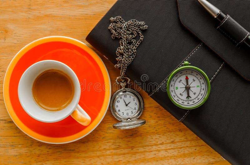 Copo alaranjado do organizador do preto do café do café com pena foto de stock royalty free