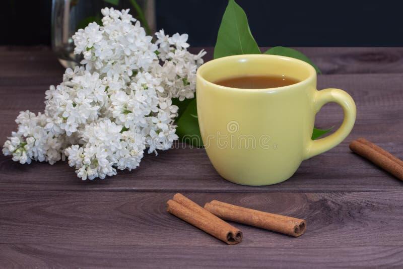 Copo amarelo do chá com canela em uma tabela de madeira escura decorada com um ramo do lilás branco Um tea party agradável com ca fotografia de stock royalty free