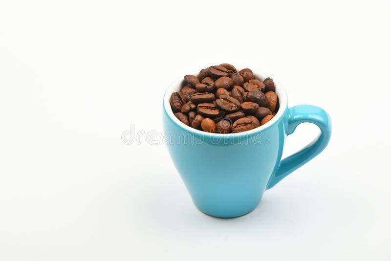Copo azul do café completamente de feijões de café sobre o branco fotografia de stock