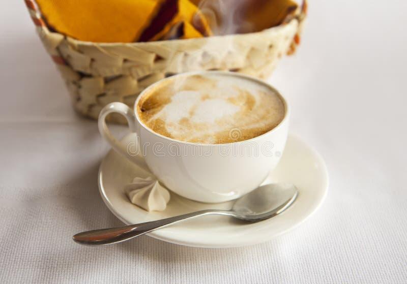 Copo branco com café cappuccino Cesta e café com um bolo pequeno e uma colher imagem de stock royalty free